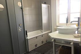 salle de bain avec baignoire, vasque, miroir et toilettes